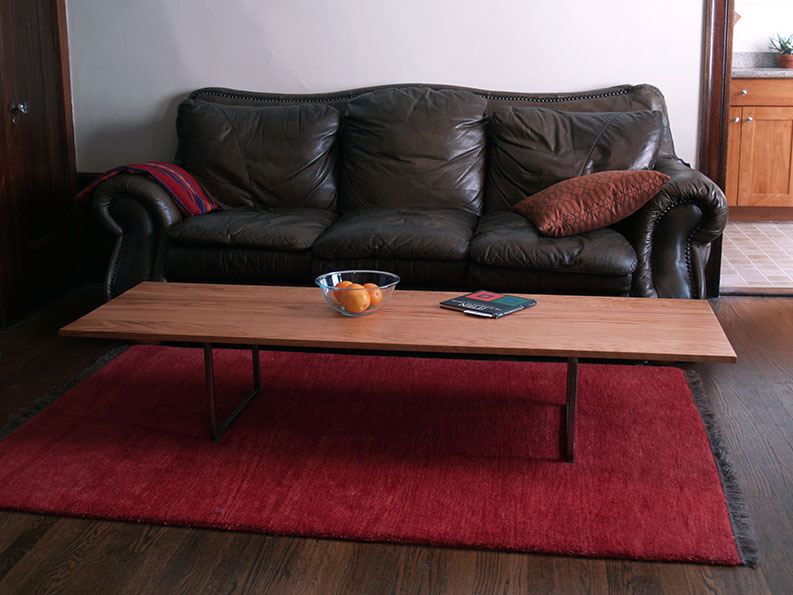 A long wooden coffee table, sitting in front of a leather couch.